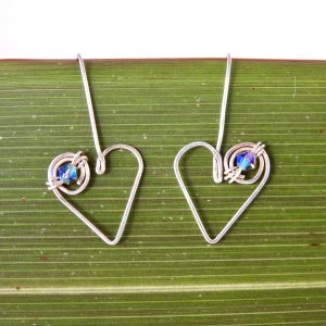 Close up of heart drop earrings showing iridescent Swarovski Crystals
