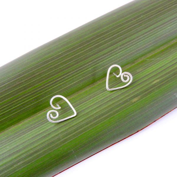 Koru Heart Studs in Eco Sterling Silver on flax leaf background