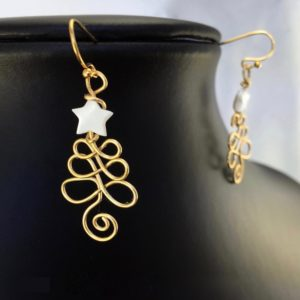 close up view of elegant wire Christmas Tree earrings with white mother of pearl star