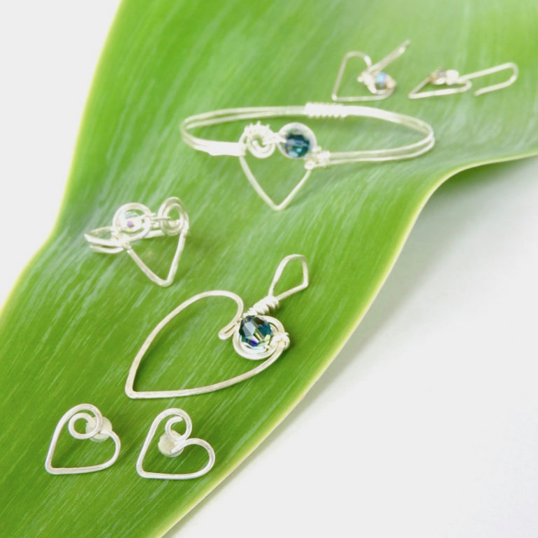 Koru Heart Collection with stud earrings, heart pendant, heart ring, heart bangle and love heart earrings on green leaf background