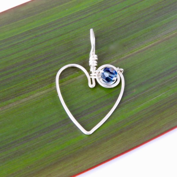 koru heart pendant in recycled sterling silver with swarovski crystal on flax background