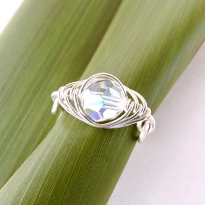 Top view of handmade eco silver pea pod birthstone ring on flax leaf