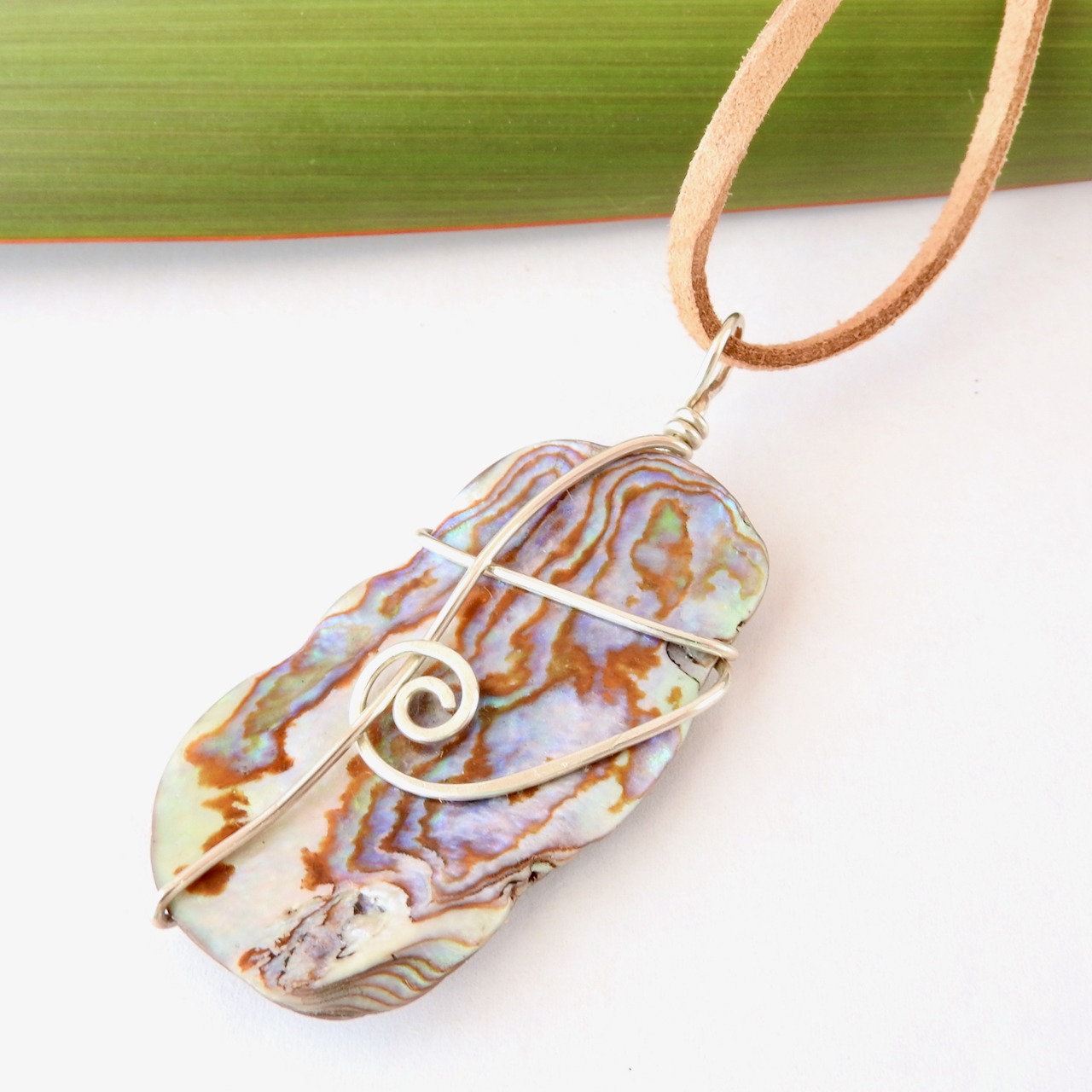 Brown Blue, cream, purple, green and pink hues in this wirewrapped paua necklace