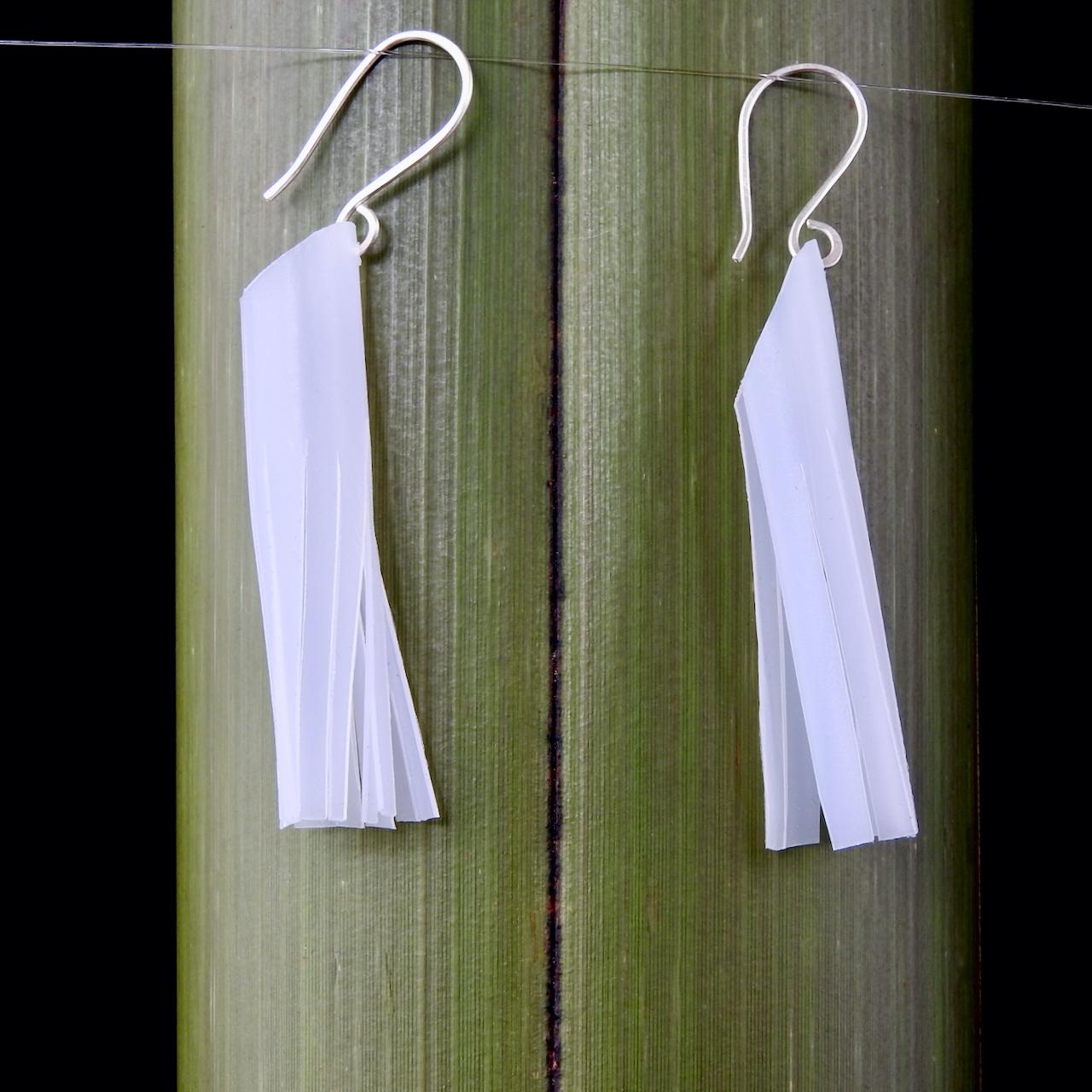 Tassel Earrings handmade from milk bottles_Hanging against flax