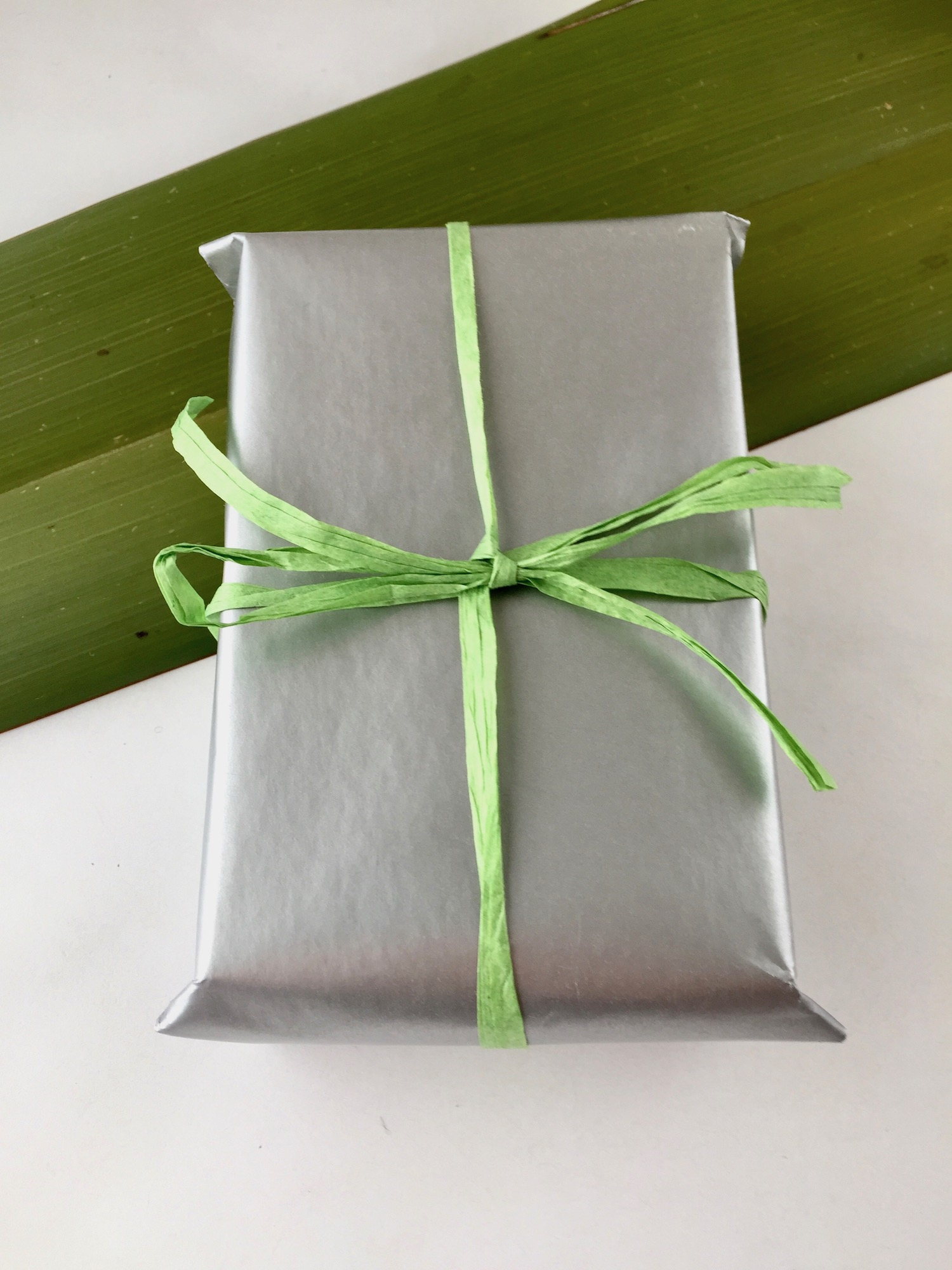 Gift wrapped box with green paper ribbon